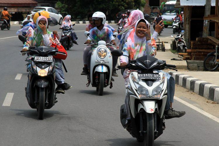 Sejumlah pelajar Sekolah Menengah Kejuruan (SMK) Negeri 1 Idi Rayeuk melakukan konvoi seusai corat-coret seragam dan melaksanakan Ujian Nasional Berbasis Komputer (UNBK) 2018 di Jalan Lintas Nasional Medan-Banda Aceh di Desa Gampong Aceh, Idi Rayeuk, Aceh Timur, Aceh, Kamis (19/4/2018). Meskipun pihak sekolah telah mengeluarkan larangan konvoi dan corat coret seragam seusai mengikuti UNBK, tapi para pelajar tetap melakukannya.