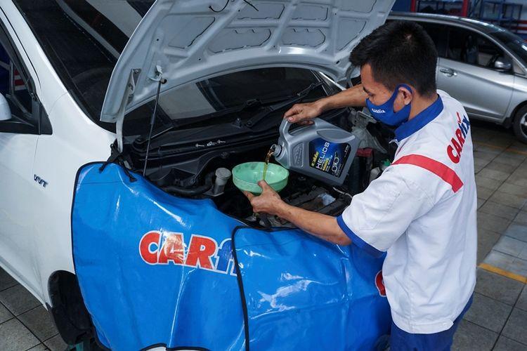 seorang mekanik tengah melakukan pengisian oli mesin mobil di bengkel carfix