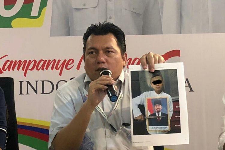 Direktur Direktur Hukum dan Advokasi TKN Jokowi-Maruf Irfan Pulungan menunjukan foto yang diduga bentuk kebencian terhadap simbol negara oleh anak-anak, di Posko Cemara, Jumat (9/11/2018).