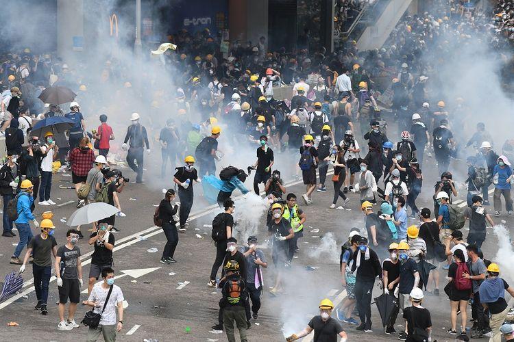 Massa pengunjuk rasa bereaksi setelah polisi Hong Kong mulai menembakkan gas air mata dalam aksi menentang UU Ekstradisi, Rabu (12/6/2019).