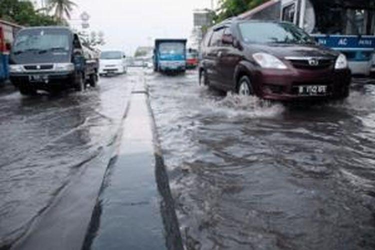 Pengguna jalan melintas di genangan air akibat hujanderas di Jalan Raya anggano, Jakarta Utara, Selasa (29/10). Buruknya kondisi saluran air di kawasan tersebut menyebabkan beberapa titik genangan di ruas Jalan RE Martadinata dan Jalan Raya Enggano usai hujan turun.