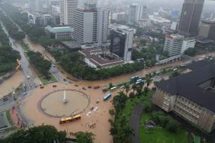 Banjir di kawasan bundaran air mancur di samping Patung Arjuna Wiwaha, Jalan MH Thamrin, Jakarta, Senin (9/2/2015). Curah hujan yang tinggi mengakibatkan sejumlah tempat di ibu kota terendam banjir. KOMPAS / LASTI KURNIA
