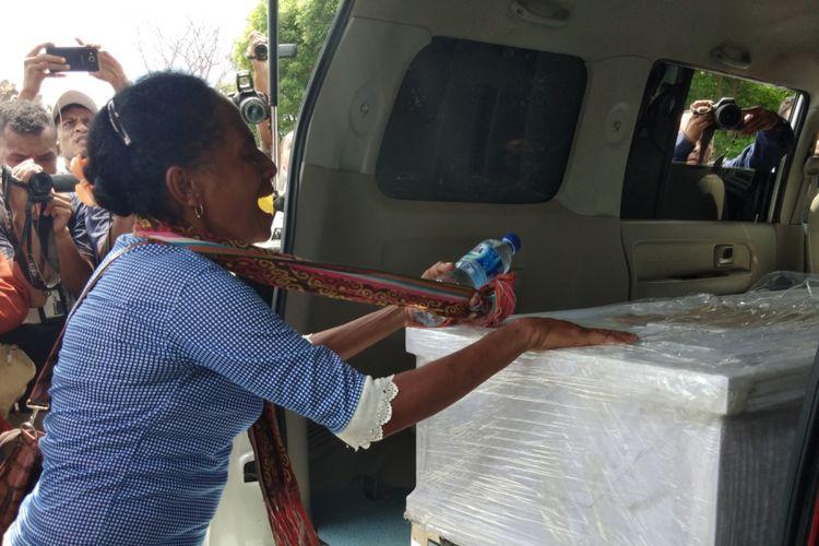 Salah seorang kerabat TKI Adelina, saat menangis mendekati peti jenazah Adelina yang dimasukan ke dalam mobil jenazah di Bandara El Tari Kupang, Sabtu (17/2/2018)