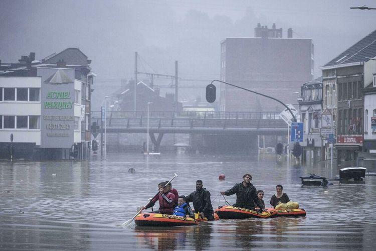 Warga menggunakan rakit karet di tengah banjir setelah Sungai Meuse jebol saat banjir besar di Liege, Belgia, Kamis, 15 Juli 2021.