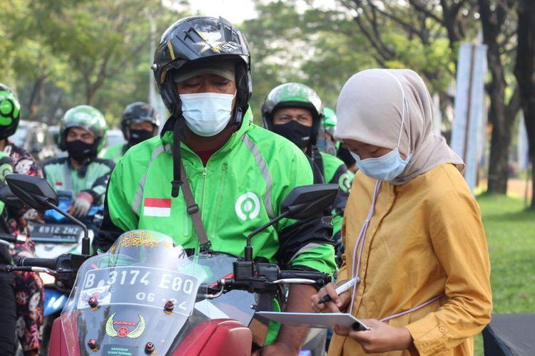 Pengemudi ojek online sedang menjalani pemeriksaan kesehatan sebelum melakukan vaksinasi Covid-19 secara drive thru di Sentra Vaksinasi Indonesia Bangkit, RS Universitas Indonesia, Depok, Rabu (2/6/2021).