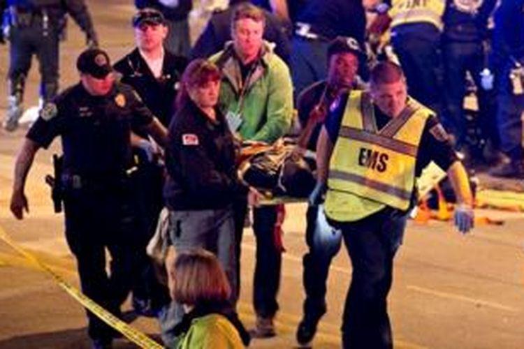Petugas medis mengangkat seorang korban cedera yang disebabkan sebuah mobil yang menabrak kerumunan penonton festival SXSW di Austin, Texas, Kamis (13/3/2014).