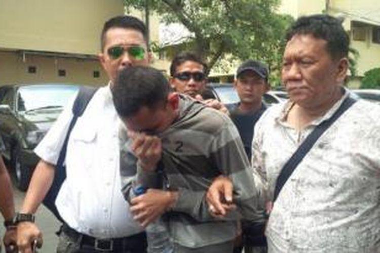 RS, pembunuh Alfi saat digiring ke kantor Ditreskrimum Polda Metro Jaya, Rabu (15/4/2015) siang.
