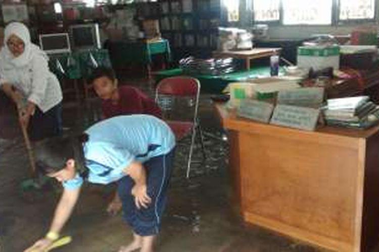 Siswa SMA Negeri 9 Bandung tengah membersihkan perpustakaan yang terendam banjir. KOMPAS.com/Putra Prima Perdana.