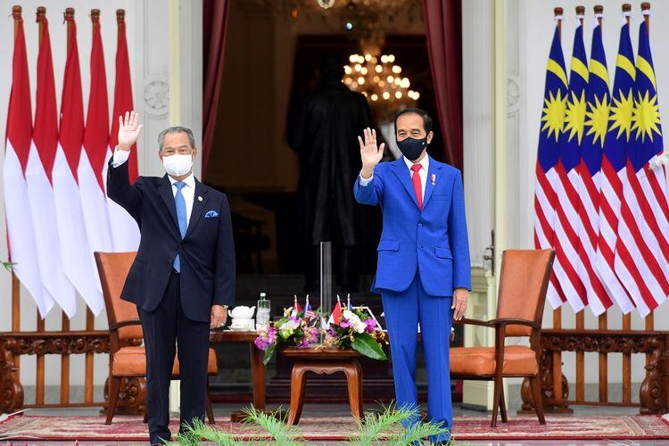 President Joko Widodo (right) and Malaysian Prime Minister Muhyiddin Yassin (left) wave their hands on the veranda of the Merdeka Palace in Jakarta on Friday (5/2/2021). ANTARA FOTO/Setpres/Laily Rachev/Handout/sgd/wsj.