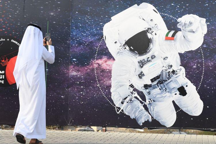 Foto ini diambil pada 25 September 2019. Seorang pria mengambil gambar ilustrasi yang menggambarkan seorang astronot dengan bendera nasional Uni Emirat Arab (UEA) di Mohammed Bin Rashid Space Center (MBRSC) di Dubai. Misi luar angkasa Arab pertama ke Mars, rencananya akan diluncurkan bulan depan untuk mempelajari atmosfer Planet Merah. Misi ini dirancang untuk menginspirasi kaum muda di kawasan itu dan membuka jalan bagi terobosan ilmiah, kata para pejabat pada 9 Juni 2020. (Foto oleh KARIM SAHIB / AFP)