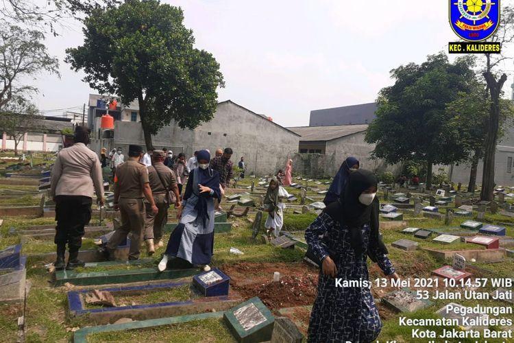 Satpol PP menghalau peziarah di TPU Utan Jati, Kalideres , Jakarta Barat, Kamis (13/5/2021).