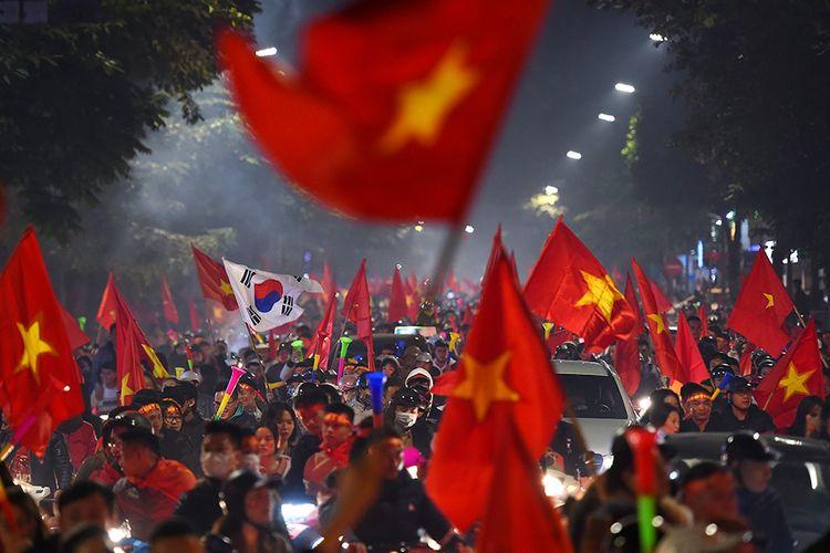 Orang-orang turun ke jalanan di Hanoi, Vietnam, merayakan kemenangan Timnas Vietnam atas Indonesia dalam pertandingan final sepak bola putra SEA Games 2019, Selasa (10/12/2019). Vietnam berhasil meraih medali emas sepak bola SEA Games setelah menundukkan Indonesia pada laga final dengan skor 3-0.