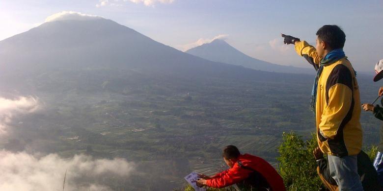 Salah seorang pendaki menunjukkan Gunung Merbabu dan Gunung Merapi saat matahari terbit, Minggu (5/4/2015) pagi.
