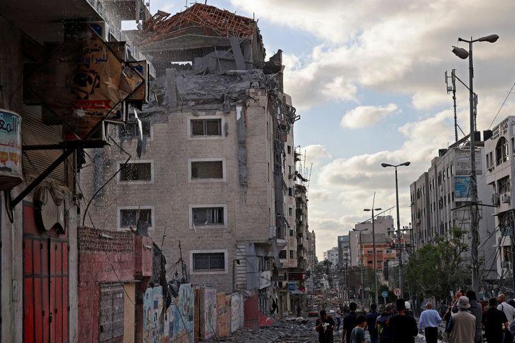 Terlihat sebuah gedung yang terdiri dari kantor Bulan Sabit Merah Qatar dibom dalam serangan udara Israel di Kota Gaza pada Senin (17/5/2021). [MOHAMMED ABED/AFP]