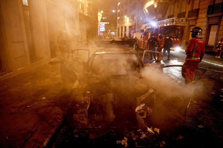 Petugas pemadam kebakaran memadamkan api yang membakar sebuah mobil di dekat Champs-Elysees, Paris, Perancis, Minggu (23/8/2020). Kerusuhan terjadi yang melibatkan sekelompok suporter PSG, usai tim jagoan mereka kalah dari Bayern Muenchen di final Liga Champions 2019/2020.