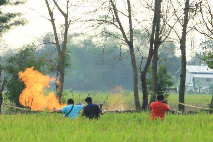 Warga saat melihat semburan api di Desa Sukaperna, Kecamatan Tukdana, Kabupaten Indramayu, Sabtu (3/4/2021). (Tribun Jabar/ Handhika Rahman)