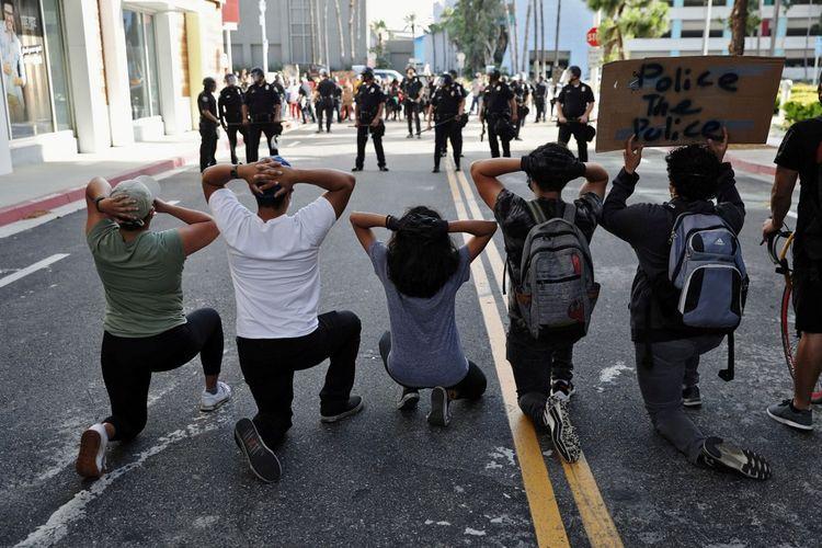 Pengunjuk rasa membawa poster saat mereka berdemonstrasi dalam unjuk rasa di seluruh negeri menyusul kematian George Floyd saat ditahan oleh polisi Minneapolis, di Long Beach, California, Amerika Serikat, Minggu (31/5/2020). ANTARA FOTO/REUTERS/Patrick T. Fallon/wsj/cfo