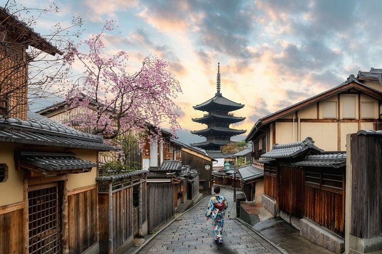 Seorang wanita mengenakan pakaian tradisional Jepang sedang berjalan-jalan di Kyoto, Jepang.