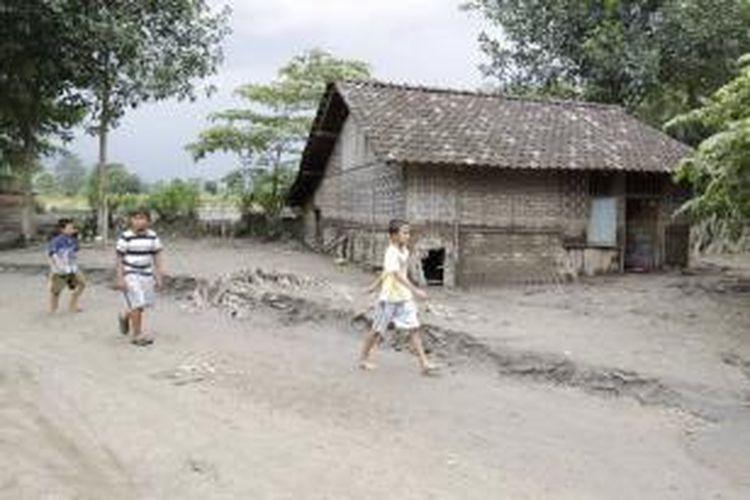 Anak-anak melintas di antara rumah yang tertimbun lahar hujan di sekitar aliran Sungai Konto, Desa Darmawulan, Kediri, Jawa Timur, 19 Februari 2014. Lahar dingin erupsi Gunung Kelud yang membawa material vulkanik ini merusak ratusan hektar sawah dan merusak bangunan yang berdiri di sisi sungai.