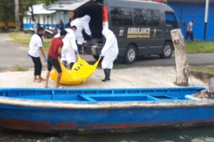 Aparat Polsek Baguala menggunakan Alat Pelindung DIri (APD) saat mengevakuasi seorang ABK yang tewas diatas perahu di Teluk Ambon, Minggu (26/4/2020)