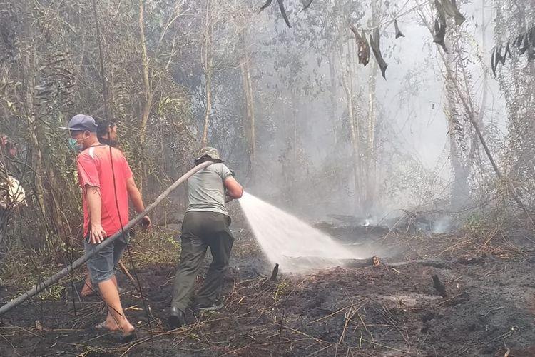 Petugas gabungan berupaya memadamkan karhutla mendekati rumah warga di Desa Rimbo Panjang, Kecamatan Tambang,  Kabupaten Kampar, Riau, Selasa (17/9/2019).