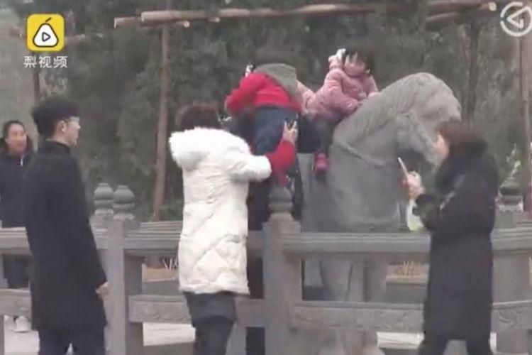 Anak-anak terlihat menunggangi patung kuda dari batu itu dengan dibantu orangtuanya. (SCMP)