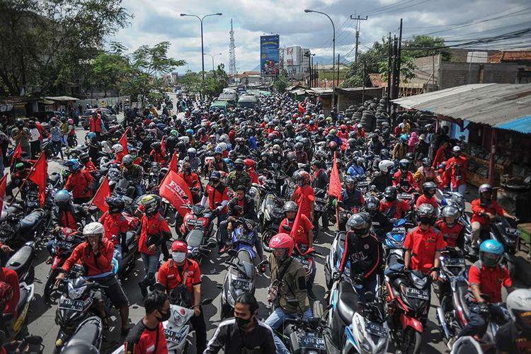 Ratusan buruh memblokir jalan nasional Bandung-Garut-Tasikmalaya saat melakukan aksi di Rancaekek, Kabupaten Bandung, Jawa Barat, Selasa (6/10/2020). Aksi tersebut merupakan buntut dari penolakan buruh terhadap pengesahan UU Cipta Kerja yang telah disahkan oleh DPR.