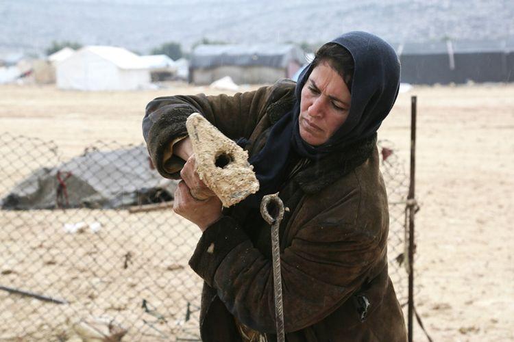 Seorang perempuan Suriah tengah membangun tenda di kamp penampungan Kalbeed, yang berada di perbatasan Suriah dan Turki.