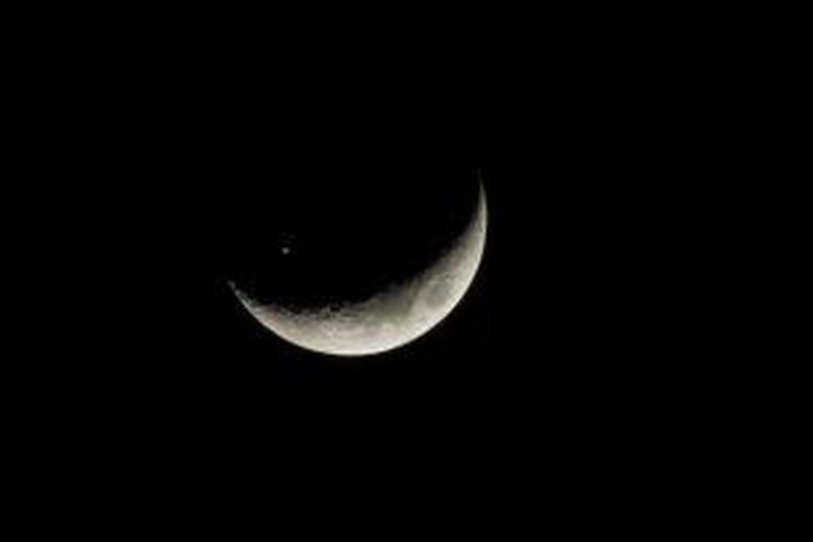 Stasiun Luar Angkasa Internasional (ISS) terpotret melintasi bulan sabit.