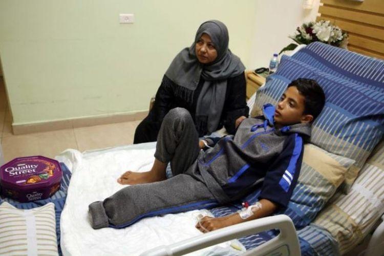 Adel Rahman Nawfal (12) berbaring di ranjangnya di rumah sakit, ditemani oleh neneknya. (AFP/Abbas Momani)