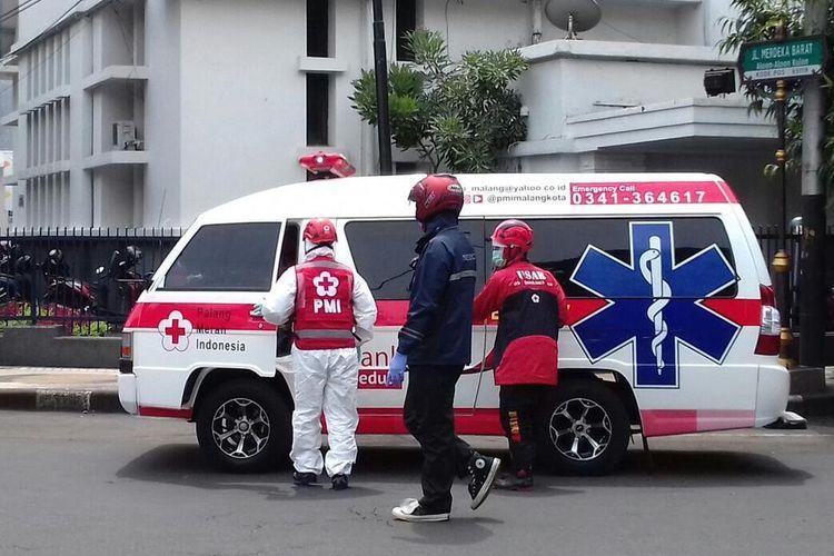 Sejumlah petugas dengan APD lengkap menggunakan mobil ambulance melintas di sekitar alun-alun Kota Malang, Jumat (27/3/2020).