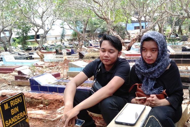 Fitri Rahmayani (kanan) dan Irwan (kiri) di pemakaman Akbar Alamsyah di makam tanah wakaf, Cipulir, Kebayoran Lama, Jakarta Selatan, Jumat (11/10/2019)