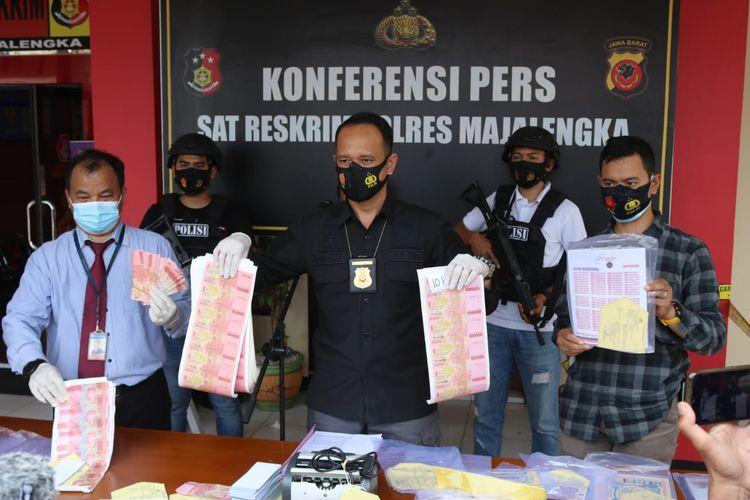 Polisi saat menunjukan barang bukti uang palsu yang hendak diedarkan mantan pegawai bank di Majalengka, Jawa Barat.