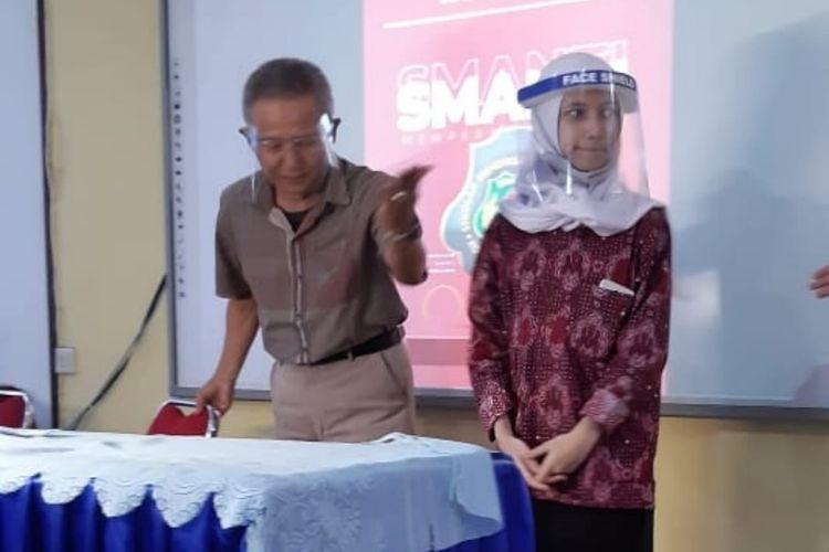 Wakil Kepala Bidang Kesiswaan SMAN 3 Kota Sukabumi Mamat Abdurahmat (kiri) bersama siswa baru Almira (kanan) saat penutupan Pengenalan Lingkungan Sekolah (PLS) di SMAN 3 Kota Sukabumi, Jawa Barat, Juli 2020.