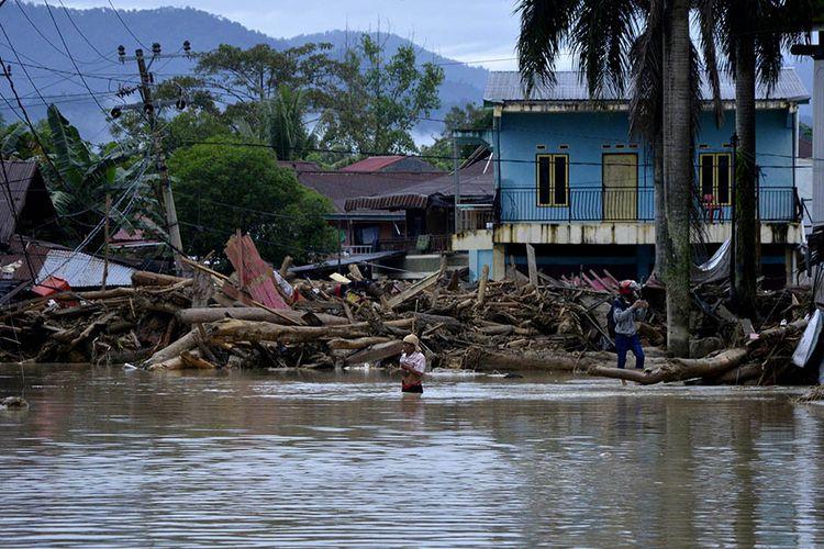 Warga melintas di sekitar rumah yang tertimbun lumpur dan batang pohon akibat terjangan banjir bandang di Kecamatan Masammba, Kabupaten Luwu Utara, Sulawesi Selatan, Rabu (15/7/2020). Banjir bandang yang terjadi akibat tingginya curah hujan tersebut mengakibatkan 16 orang meninggal dunia dan puluhan warga dilaporkan masih dalam pencarian, sementara ratusan rumah rusak berat dan hilang.