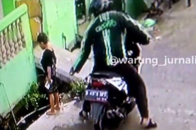 Seorang penjambret yang mengenakan jaket berlogo Grabike terekam CCTV menjambret seorang anak di Cengkareng, Jakarta Barat.