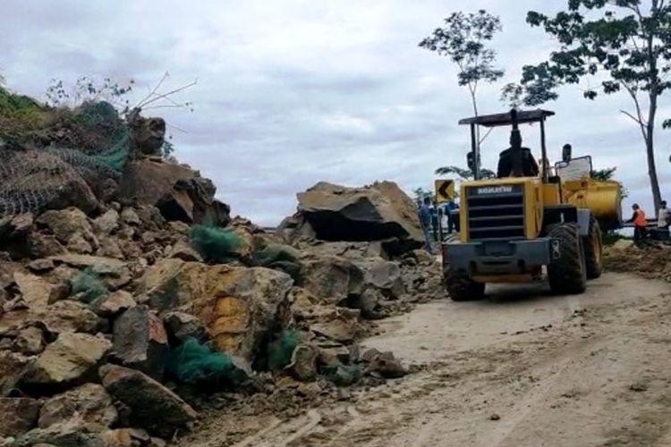 Alat berat tengah membersihkan material longsor yang menutupi sebagian badan jalan di ruas jalan lintas selatan Cianjur, Jawa Barat, akibat tebing hejo di tajnjakan Mala Naringgul Cianjur, longsor, Rabu (17/2/2021)