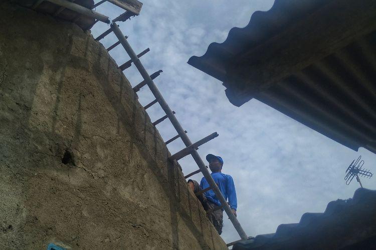 Seorang warga memperbaiki genting yang rusak diterjang angin puting beliung di Desa Ubrug, Kecamatan Warungkiara, Sukabumi, Jawa Barat, Kamis (30/1/2020).