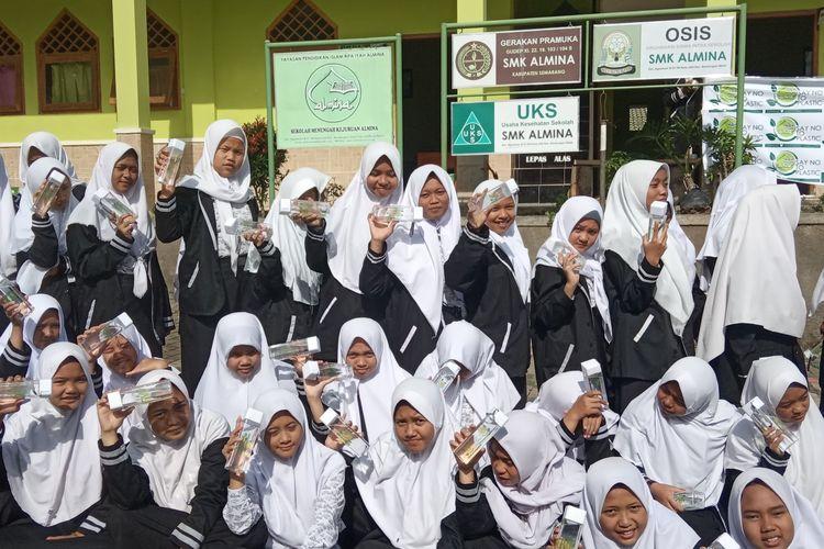 Siswa SMK Al Mina menunjukan botol minum untuk mengurangi sampah plastik.