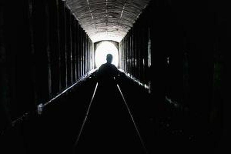 Warga berjalan melintasi terowongan jalur kereta api di Lampegan, Cibeber, Cianjur, Jawa Barat, jalur penghubung kereta api Cianjur Sukabumi, Senin (7/4/2014). Terowongan tertua di Indonesia dengan panjang 686 meter ini dibangun tahun 1879-1882 oleh Staats Spoorwegen, perusahaan kereta api masa Hindia Belanda.