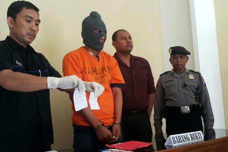 Foto : Paur Subag Humas Polres Madiun Kota, Aiptu Mashudi menunjukkan barang bukti dan tersangka kasus perjudian togel online di Mapolres Madiun Kota, Rabu ( 25 /1/2017).