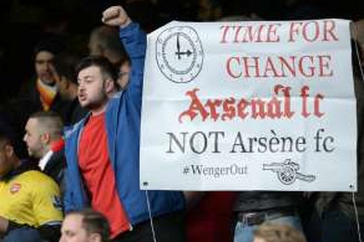 Suporter Arsenal membawa kertas bertuliskan pesan agar Arsene Wenger mundur dari jabatannya sebagai Manajer Arsenal.