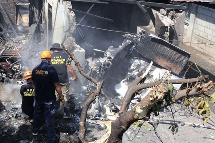 Petugas memeriksa lokasi jatuhnya pesawat yang menimpa rumah di Filipina, Sabtu (17/3/2018).