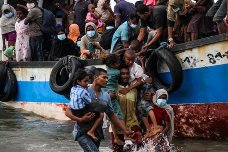 Warga melakukan evakuasi paksa pengungsi etnik Rohingya dari kapal di pesisir pantai Lancok, Kecamatan Syantalira Bayu, Aceh Utara, Aceh, Kamis (25/06).