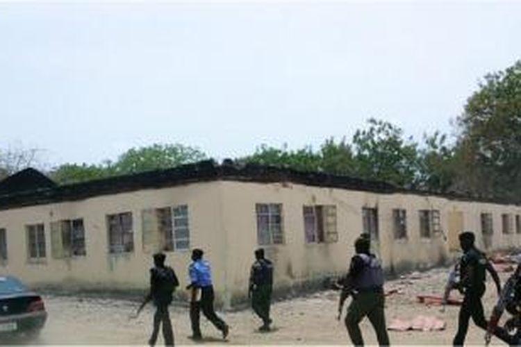 Aparat keamanan Nigeria berjalan melintasi sekolah menengah khusus perempuan di kota Chibok, Nigeria yang dibakar kelompok militan Boko Haram. Kelompok militan itu juga menculik ratusan siswi sekolah itu dan dikabarkan menjual mereka ke luar negeri.