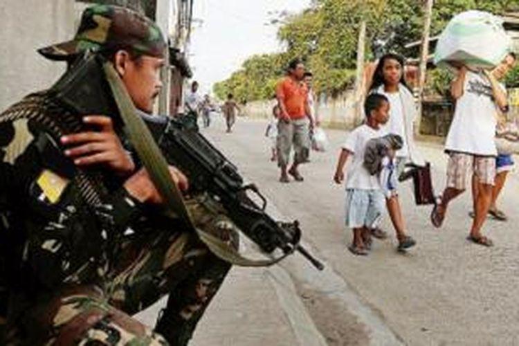 AP Photo/Bullit Marquez  Tentara Filipina berjaga-jaga di kota Zamboanga, Filipina selatan, saat warga berbondong-bondong meninggalkan tempat tinggal mereka menyusul ketegangan antara gerilyawan pemberontak dan pasukan pemerintah yang memasuki hari kedua, Selasa (10/9). Sekitar 200 gerilyawan menjadikan penduduk sebagai perisai manusia di desa-desa tersebut.