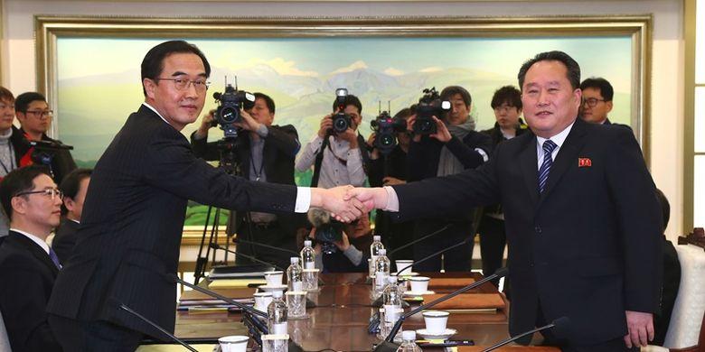 Menteri Unifikasi Korea Selatan Cho Myung Gyun (kiri) berjabat tangan dengan pemimpin delegasi Korea Utara Ri Son Gwon (kanan) dalam pertemuan resmi di Panmunjom, di Zona Demiliterisasi, Selasa (9/1/2018). (AFP/Dong A Ilbo)