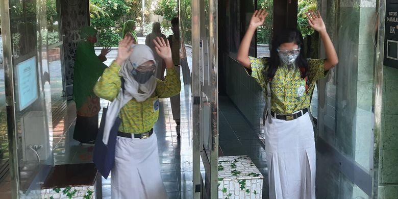 Para siswa kelas IX SMPN 4 Solo melewati bilik antiseptik yang terpasang di pintu masuk utama sekolah, Rabu (4/11/2020).