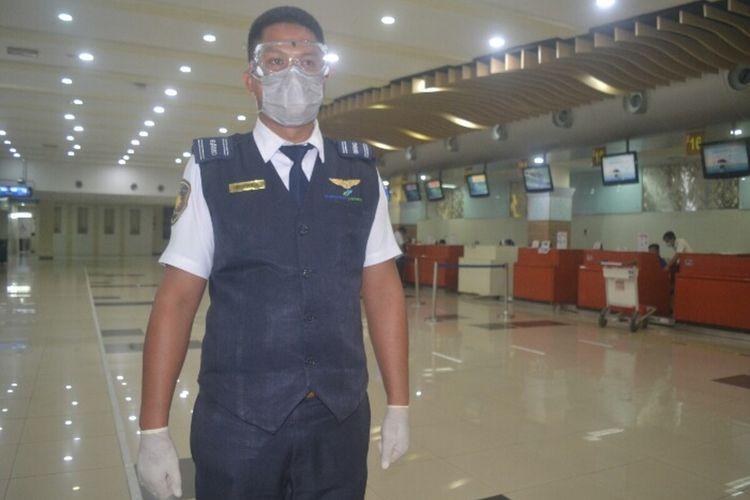 Petugas Avsek Bandara Sam Ratulangi dilengkapi APD berdiri di belakang Check In yang lengang