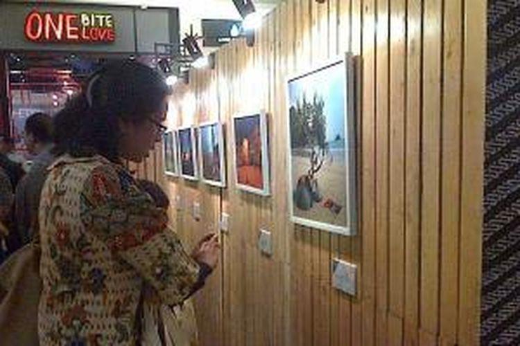 Pengunjung melihat pameran foto 'Melihat Indonesia, Ekspedisi Sabang-Merauke: Kota dan Jejak Peradaban' di lantai dasar Food Society Kota Kasablanka, Jakarta, Senin (30/12/2013). Pameran ini akan terselenggara hingga 5 Januari 2014.